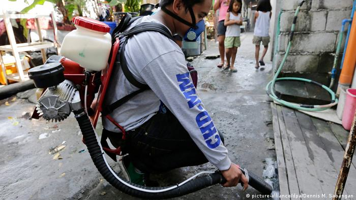 A man sprays anti-mosquito spray in Philippines