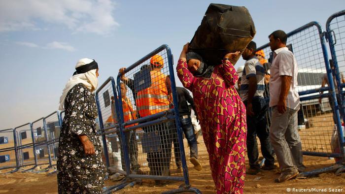 Syrian Kurdish refugees cross the border into Turkey