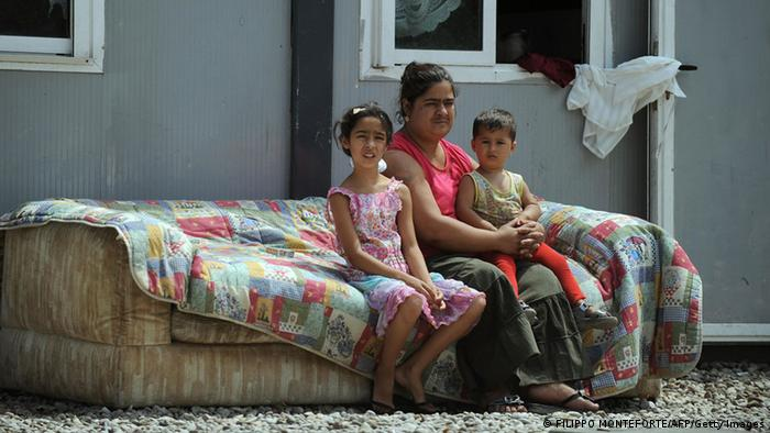 A Roma woman and two children sit on a couch outside their home during a meeting with a humanitarian organization in their camp on the outskirts of Rome. Photo: FILIPPO MONTEFORTE/AFP/Getty Images