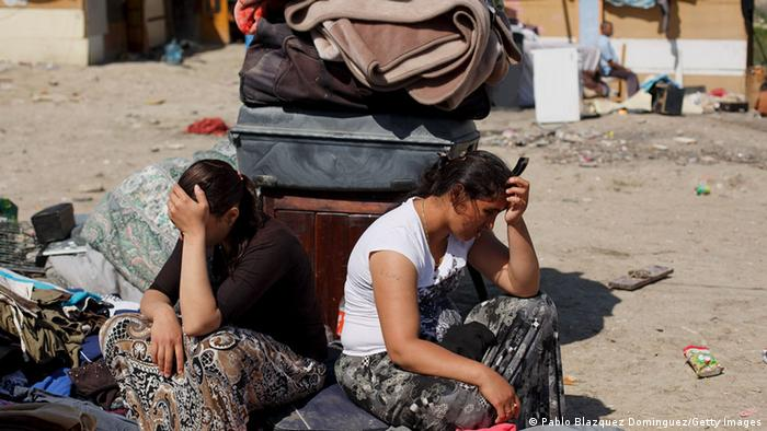 Roma women sit head in hands next to the belongings they could save after their hut was demolished at 'el Gallinero' shanty town on April 9, 2014 in Madrid, Spain. Photo by Pablo Blazquez Dominguez/Getty Images
