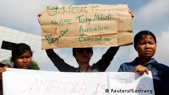 People hold signs during a protest against Cambodia's plans to resettle intercepted refugees, near the Australian embassy in Phnom Penh September 26, 2014.