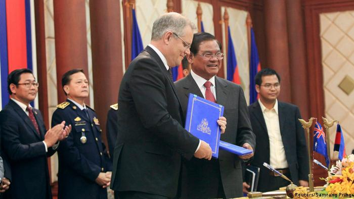 Australia's then Immigration Minister Scott Morrison (centre, L) exchanges documents with Cambodian Deputy Prime Minister and Interior Minister Sar Kheng (centre, R) after a signing ceremony between Cambodia and Australia relating to the settlement of refugees, at the Interior Ministry in Phnom Penh September 26, 2014.