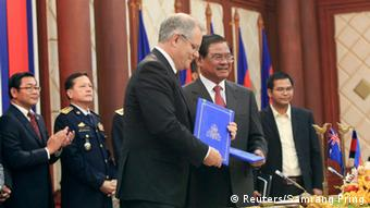 Australia's Immigration Minister Scott Morrison (centre, L) exchanges documents with Cambodian Deputy Prime Minister and Interior Minister Sar Kheng (centre, R) after a signing ceremony between Cambodia and Australia relating to the settlement of refugees, at the Interior Ministry in Phnom Penh September 26, 2014 (Photo: REUTERS/Samrang Pring)