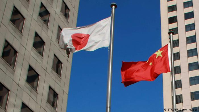 A Chinese national flag (C) and a Japanese national flag (L) flying before two buildings in the Chinese city of Dalian (Photo: STR/AFP/Getty Images)