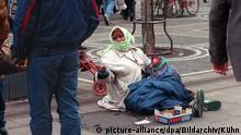 Mit einem Kleinkind auf dem Schoß sitzt eine junge Frau im Dezember 1992 auf der Frankfurter Einkaufsmeile Zeil und bittete Passanten um Almosen.