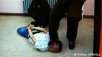 man on floor, lying on face, other men hold him in place with feet