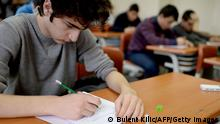 Bildunterschrift:TO GO WITH AFP STORY IN FRENCH BY AMBRE TOSUNOGLU Students sit behind school desks during an exam on January 4, 2014 at the Firat Education Center in Istanbul. Fem Dershane welcomes in a brand new decor nearly 800 students who are preparing for university admission exams. AFP PHOTO/BULENT KILIC (Photo credit should read BULENT KILIC/AFP/Getty Images)