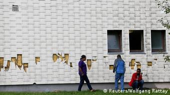 Drei Flüchtlinge stehen vor der beschädigten Fassade eines Hauses (Foto: Reuters)