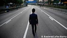 A man walks along an empty street near the central financial district in Hong Kong September 30, 2014. Tens of thousands of pro-democracy protesters extended a blockade of Hong Kong streets on Tuesday, stockpiling supplies and erecting makeshift barricades ahead of what some fear may be a push by police to clear the roads before Chinese National Day. REUTERS/Carlos Barria (CHINA - Tags: POLITICS CIVIL UNREST TPX IMAGES OF THE DAY)