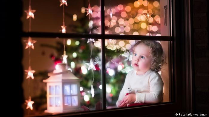 Girl looking through window at Christmas time (Fotolia/famveldman)