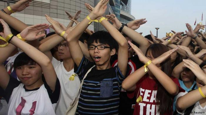 Joshua Wong with his arms up protesting in Hong Kong