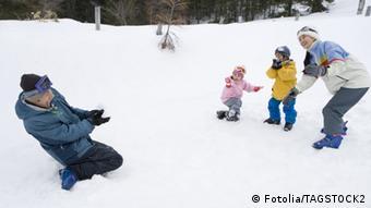 Symbolbild Schneeballschlacht: ein Mann (links) wird von seinen beiden Kindern und seiner Frau (rechts) mit Schneebällen beworfen