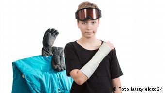 Symbolbild Skiunfall: Ein Junge mit eingegipstem rechten Arm, eine Skibrille auf dem Kopf. Im Hintergrund Skikleidung