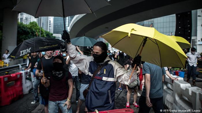 Protests in Hongkong, with people holding umbrellas.