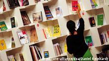 Eine Frau sortiert auf der Buchmesse in Frankfurt am Main am 08.10.2013 Bücher in einem Regal im Pavillon des Gastlandes Brasilien. Die weltweit größte Messe ihrer Art dauert noch bis zum 13. September. Foto: Daniel Reinhardt/dpa