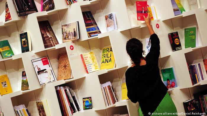 Mulher pega livro em estante de livraria