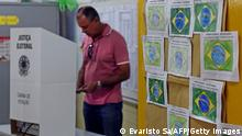 A man casts his vote at a polling station inside a public school in Brasilia, Brazil on October 05, 2014. More than 142 million Brazilians went to the polls Sunday in presidential and legislative elections to cap a dramatic campaign. Leftist incumbent Dilma Rousseff was expected to top the presidential poll but fail to secure the 50 percent necessary to avoid a run-off vote on October 26 against either social democrat Aecio Neves or environmentalist Marina Silva. AFP PHOTO/EVARISTO SA (Photo credit should read EVARISTO SA/AFP/Getty Images)