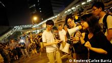 A student speaks as protesters block the main street to the financial Central district outside of the government headquarters building in Hong Kong October 5, 2014. Some Hong Kong pro-democracy protesters, many in tears, began leaving the Mong Kok area of the city late on Sunday, pulling back from the scene of recent clashes with those who back the pro-Beijing government. Fearing a police crackdown may come within hours, other protesters who have paralysed parts of the Asian financial hub with mass sit-ins also pulled back from outside Hong Kong Chief Executive's office, with police removing barricades nearby. REUTERS/Carlos Barria (CHINA - Tags: CIVIL UNREST POLITICS BUSINESS)