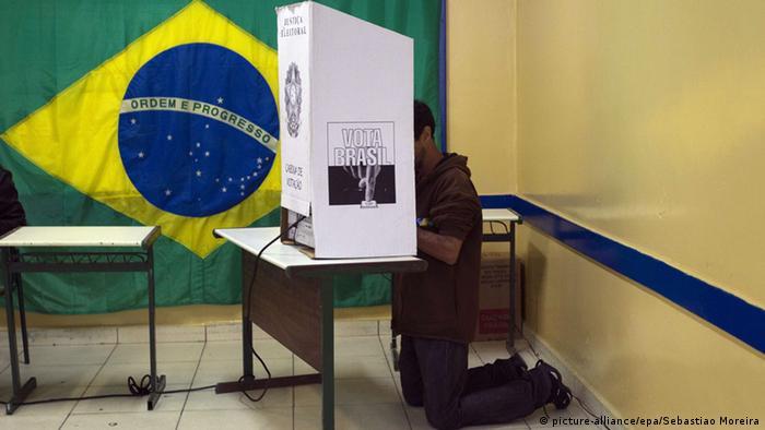 Eleitor na cabine de votação com bandeira do Brasil ao fundo