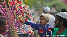A Muslim boy buys a paper fly-wheel during the celebrations to mark Eid al-Adha in the northern Indian city of Chandigarh October 6, 2014. Muslims around the world celebrate Eid al-Adha by the sacrificial killing of sheep, goats, cows and camels to commemorate Prophet Abraham's willingness to sacrifice his son Ismail on God's command. REUTERS/Ajay Verma (INDIA - Tags: RELIGION)