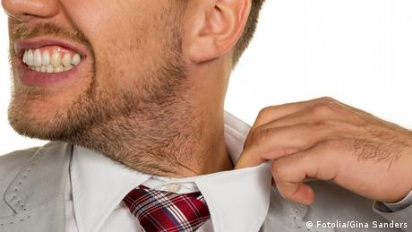 Ein Mann zerrt an seinem Hemdkragen