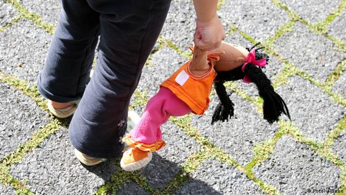 Menina segura uma boneca de pano