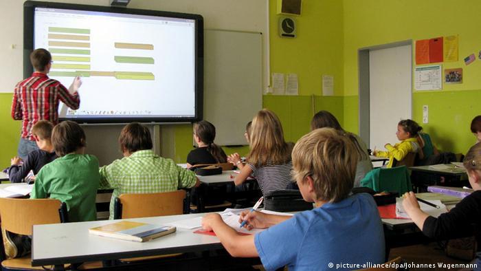 Lehrer in Klassenzimmer, der den Schülern etwas auf einem Monitor erklärt