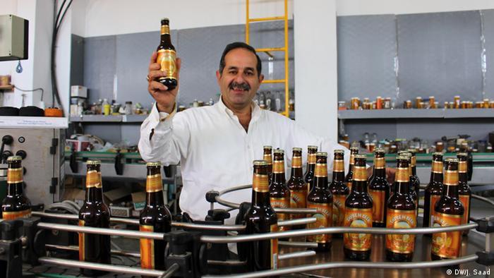 Nadim Khoury, fundador da cerveja palestina Taybeh em sua linha produção com uma garrafa de cerveja na mão