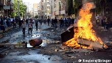 Kurdish protesters set fire to a barricade set up to block the street as they clash with riot police in Diyarbakir October 7, 2014. At least 12 people died on Tuesday during violent clashes across Turkey, local media reported, as the fate of the besieged Syrian border town of Kobani stirred up decades of tensions with Turkey's Kurdish minority. Violence erupted in Turkish towns and cities mainly in the Kurdish southeastern provinces, as protesters took to the streets to demand the government do more to protect Kobani, a predominantly Kurdish settlement which has been surrounded by Islamic State fighters for three weeks. Picture taken October 7, 2014. REUTERS/Stringer (TURKEY - Tags: POLITICS CIVIL UNREST CONFLICT)