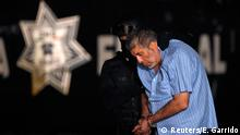 A federal policeman escorts Vicente Carrillo, drug kingpin of the Juarez Cartel, at the hangar belonging to the office of the Attorney's General in Mexico City October 9, 2014. Mexico captured the leader of the once-feared Juarez Cartel in the country's restive north on Thursday, the second drug kingpin to fall in just over a week, a government source said. Vicente Carrillo, 51, long-time head of the Juarez Cartel, was a fierce rival of Joaquin Shorty Guzman, the leader of the Sinaloa Cartel and the world's most wanted drug boss until his capture in February. REUTERS/Edgard Garrido (MEXICO - Tags: CRIME LAW CIVIL UNREST DRUGS SOCIETY POLITICS)