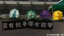 A man walks past a column of umbrellas on a footbridge outside outside the government headquarters in Hong Kong October 10, 2014. Hong Kong student protesters said on Friday they were determined to maintain their campaign for full democracy, undaunted by the city government's rejection of talks aimed at defusing a standoff that has shaken communist China's capitalist hub. Chinese characters on the banner read Without protest how can there be change. REUTERS/Bobby Yip (CHINA - Tags: POLITICS BUSINESS CIVIL UNREST)