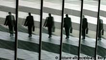 ARCHIV - ILLUSTRATION - Ein Mann mit Aktentasche geht am 22.03.2005 in Bonn ins Büro und spiegelt sich dabei in Glasscheiben. Foto: Oliver Berg/dpa (zu dpa Top-Banker bekommen neuen Bonusregeln zu spüren vom 10.10.2014) +++(c) dpa - Bildfunk+++