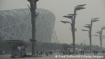 People walk near the national stadium in Beijing amid heavy smog on October 10, 2014 (Photo: FRED DUFOUR/AFP/Getty Images)