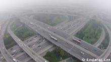 Vehicles drive on the Sihui overpass amid heavy haze and smog in Beijing, October 11, 2014. Widespread smog has affected a large part of north China including capital Beijing as the National Meteorological Center (NMC) extended a yellow alert on Thursday for air pollution, Xinhua News Agency reported. REUTERS/Jason Lee (CHINA - Tags: ENVIRONMENT HEALTH)