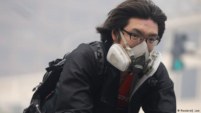 A man wearing a respiratory protection mask cycles along a road amid the heavy haze in Beijing, October 10, 2014 (Photo: REUTERS/Jason Lee)