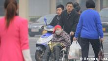 An elderly woman wearing a mask is pushed in a wheelchair through a crossing on a heavy hazy day in Beijing, October 10, 2014. Widespread smog has affected a large part of north China including capital Beijing as the National Meteorological Center (NMC) extended a yellow alert on Thursday for air pollution, Xinhua News Agency reported. REUTERS/Jason Lee (CHINA - Tags: ENVIRONMENT HEALTH)