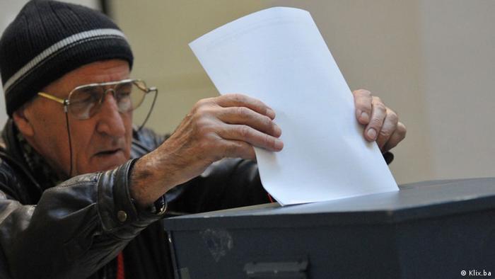 Stariji muškarac ubacuje glasački listić u kutiju
