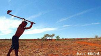Farmer in Brazil swings a ho into the parched ground