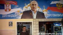 A man walks below a poster depicting Russia's President Vladimir Putin inside a newly-opened Putin bar in Novi Sad October 10, 2014. On Thursday, guns, tanks and planes will be back in Belgrade, now capital of Serbia, for a Liberation Day parade held four days early to accommodate the guest of honour -- Russian President Vladimir Putin, en route to a summit in Milan. Liberation Day marks the Nazi retreat across the River Sava on October 20, 1944, leaving the capital to the Red Army and Yugslav Partisan guerillas, and has been commemorated by memorials rather than military parades after Yugoslavia split with Josef Stalin's Soviet Union in 1948. It is a gesture with huge symbolism in a Cold-War-style East-West split over Ukraine that has forced Serbia, politically indebted to Russia but seeing its economic future with the European Union, into a delicate balancing act. Picture taken October 10, 2014. TO GO WITH STORY SERBIA-RUSSIA/EU REUTERS/Marko Djurica (SERBIA - Tags: POLITICS MILITARY BUSINESS)