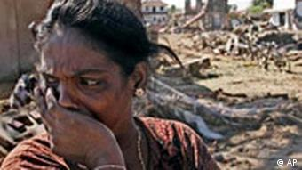 A woman holds her hand over her mouth, behind her a landscape of destruction