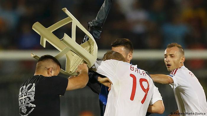 Serbischer Fan schlägt mit einem Plastikstuhl auf albanische Spieler ein. Foto: Reuters