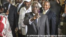 Bildunterschrift:Afonso Dhlakama, a former Renamo rebel chief turned opposition leader who is seeking the Mozambican presidency for the fifth time, shows his ink-stained finger after casting his ballot at a polling station in Maputo as Mozambique votes in presidential and legislative elections on October 15, 2014. The Renamo party candidate has lost all previous elections to candidates from erstwhile civil war foes Frelimo, crying foul each time. Mozambicans started voting in a tough electoral test for the ruling Frelimo, the party that has run the resource-rich country since independence in 1975. AFP PHOTO/GIANLUIGI GUERCIA (Photo credit should read GIANLUIGI GUERCIA/AFP/Getty Images)