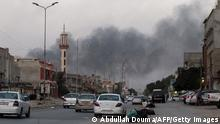 Smoke billows from buildings during clashes between Libyan security forces and armed Islamist groups in the eastern coastal city of Benghazi on August 23, 2014. Islamist fighters in the Fajr Libya (Libyan Dawn) coalition said they have captured Tripoli's battered international airport after many days of clashes with nationalist militiamen. AFP PHOTO / ABDULLAH DOMA (Photo credit should read ABDULLAH DOMA/AFP/Getty Images)