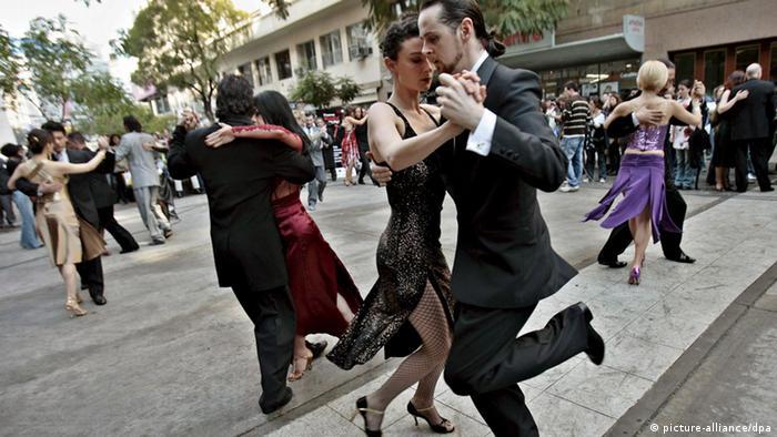 Mehrere Paare in festlicher Abendgarderobe tanzen unter freiem Himmel auf einem öffentlichen Platz