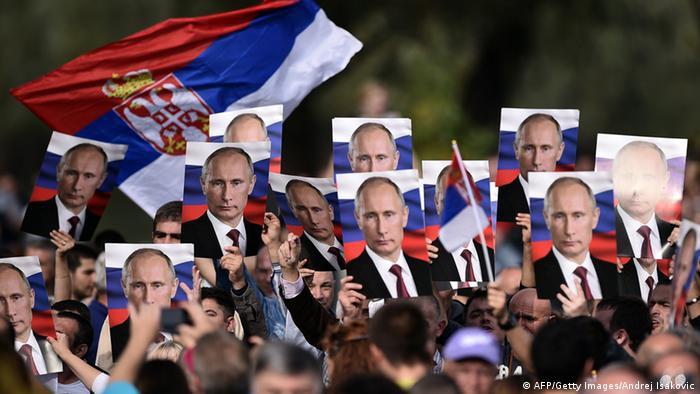 Жители Белграда держат плакаты с портретом Путина, фото из архива