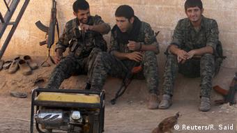 Kurdish People's Protection Units (YPG) fighters rest in the countryside near Qamishli