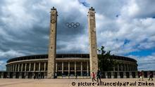 ARCHIV - Menschen gehen am 23.06.2014 in Berlin am Olympiastadion vorbei. Foto: Paul Zinken/dpa (zu dpa «Viel Lärm um deutsche Olympia-Bewerbung» vom 31.08.2014) +++(c) dpa - Bildfunk+++