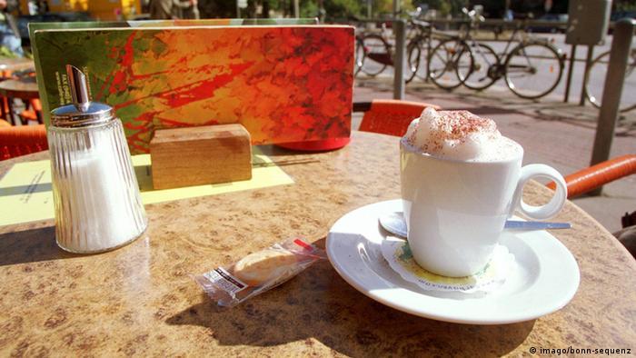In einem Straßencafé steht eine Tasse Cappuccino auf einem Tisch