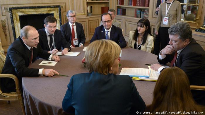 Merkel sitting at a table with Putin, Poroshenko and Hollande