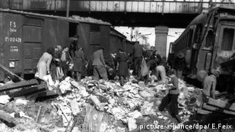 In between fear and liberation: Shortly before the end of the war, hungry civilians search for food in bombed-out freight cars